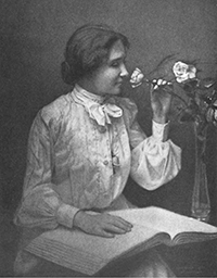 Helen Keller reading a book and smelling roses