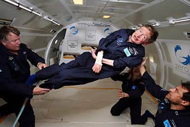 Physicist Stephen Hawking floating in zero gravity, supported by three NASA astronauts
