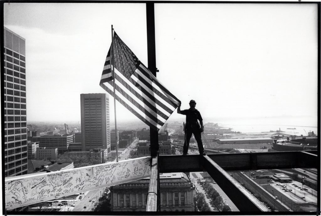 "There have been many memorable photographs taken in Cleveland, but this one by Plain Dealer photographer Christine ""Chris"" Stephens captures the city's beauty, daring, and optimism as it entered the 1990s. For journalists, the image brings mixed emotions. It shows an iron worker atop the 20-story North Point Office Tower at E. 9th Street and Lakeside Avenue, the former site of the Cleveland Press. The Press building was demolished after the newspaper closed in 1982 and it was replaced with an office building and tower. Cleveland Public Library Photograph Collection."