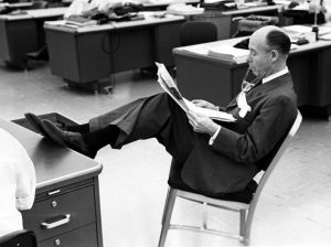 Seltzer reads an issue of the Cleveland Press in 1960 with his feet propped on one of the desks in the city room. Special Collections, Cleveland State University Library.