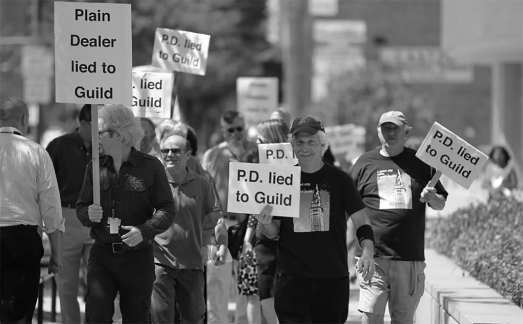 "A ""Save the PD"" rally in 2013 in front of the PD offices at E. 18th Street and Superior Avenue. A group of Newspaper Guild members organized the campaign to try to preserve jobs and what they saw as the the quality of journalism in Cleveland. Despite their efforts, the newspaper's owners layed off one-third of the editorial staff, about 50 people, on July 31, 2013, the same day they ended 7-day home delivery in favor of a ""digital first"" strategy. Photograph courtesy of Harlan Spector."