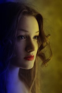 Young woman with warm yellow light on her right side of face and cold blue light on left.